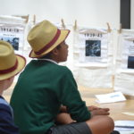 children in hats looking at a timeline for stirchley baths