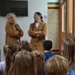 2 Women in brown coats teaching children in stirchley baths