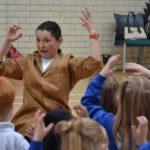 Woman in brown coat teaching children in stirchley baths